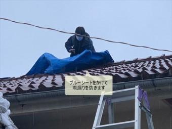 屋根にブルーシートをかけて雨養生