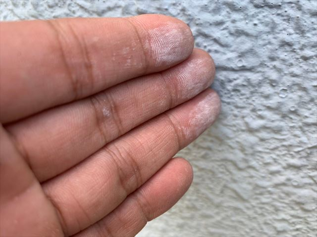 チョーキング現象が起きた外壁を触って白くなった手